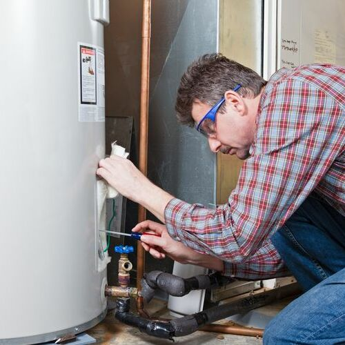 A Plumber Repairs a Water Heater.