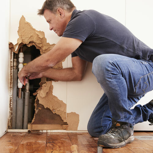 A Plumber Works on a Burst Pipe.