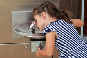 A Little Girl Stoops to Drink From a Fountain