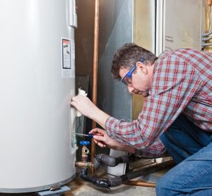 A Plumber Examines a Gas Water Heater