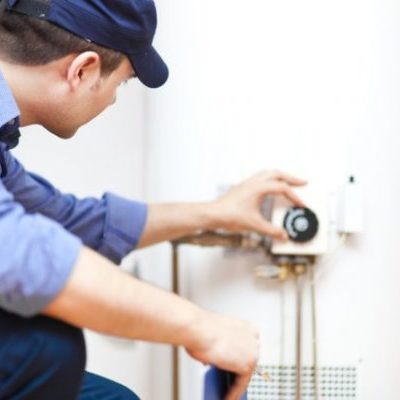A Plumber Adjusts a Water Heater.
