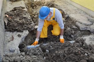 A Plumber Fixing a Sewage Pipe at a New Construction Site